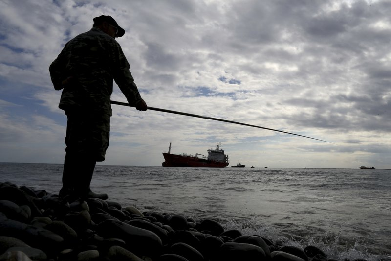 A man fishes from the shore as the tanker Athlos lays aground about 200-yards from the village of Zygi off the south coast of Cyprus, Saturday, Dec. (AP Photo/Petros Karadjias)