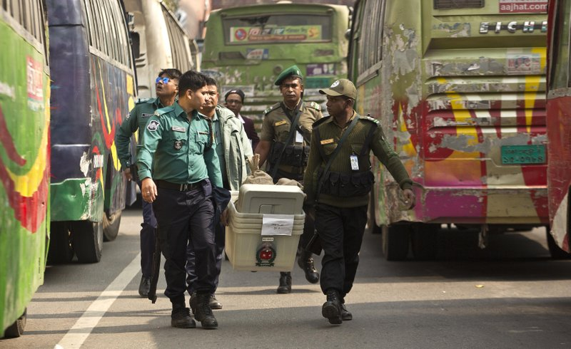 Bangladeshi security personnel carry voting material before being transported to different polling stations on the eve of the general elections in Dhaka, Bangladesh, Saturday, Dec. (AP Photo/Anupam Nath)