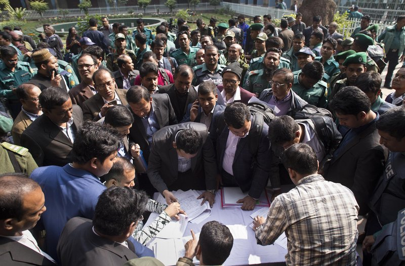 Bangladeshi elections officials gather to collect voting material at a distribution center on the eve of the general elections in Dhaka, Bangladesh, Saturday, Dec. (AP Photo/Anupam Nath)