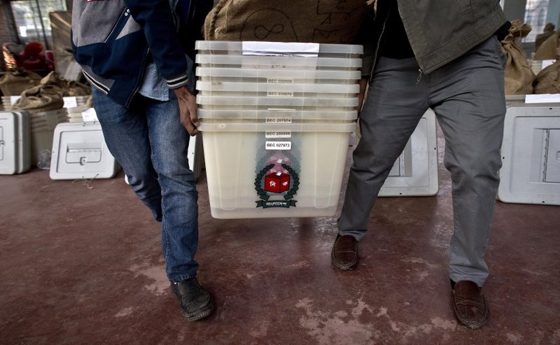 Bangladeshi election officials carry voting material at a distribution center before being transported to different polling stations on the eve of the general elections in Dhaka, Bangladesh, Saturday, Dec. (AP Photo/Anupam Nath)