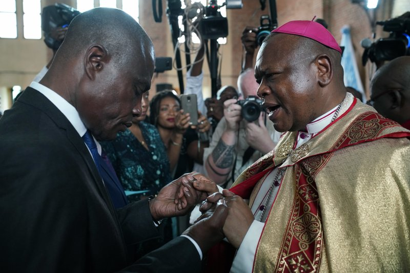 Congolese opposition presidential candidate Martin Fayulu is blessed by Msg. Fridolin Ambongo, the the newly appointed Archbishop of Kinshasa at Notre Dame du Congo cathedral in Kinshasa, Congo, Saturday Dec. (AP Photo/Jerome Delay)