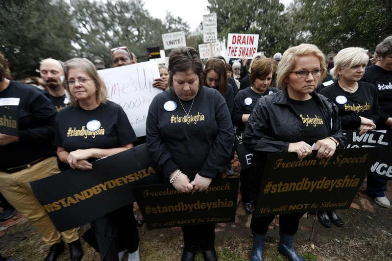 FILE - In this Jan. 11, 2018, file photo, teachers bow their heads in prayer at the start of a rally for school teacher Deyshia Hargrave, who was arrested while speaking against the superintendent's pay raise at an education board meeting earlier this week, in Abbeville, La. (AP Photo/Gerald Herbert, File)