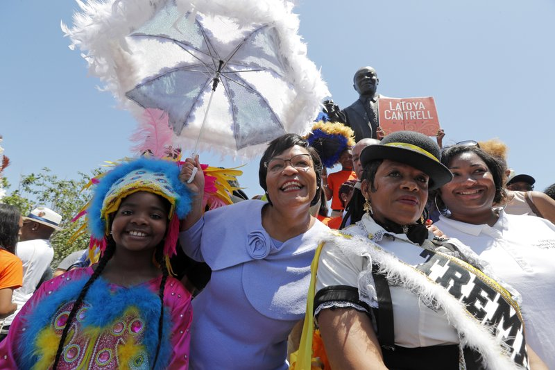FILE - In this May 7, 2018, file photo, New Orleans Mayor Latoya Cantrell, second from left, poses for a photo in front of a statue of Louis Armstrong while leading a second-line parade after her inauguration in New Orleans. (AP Photo/Gerald Herbert, File)