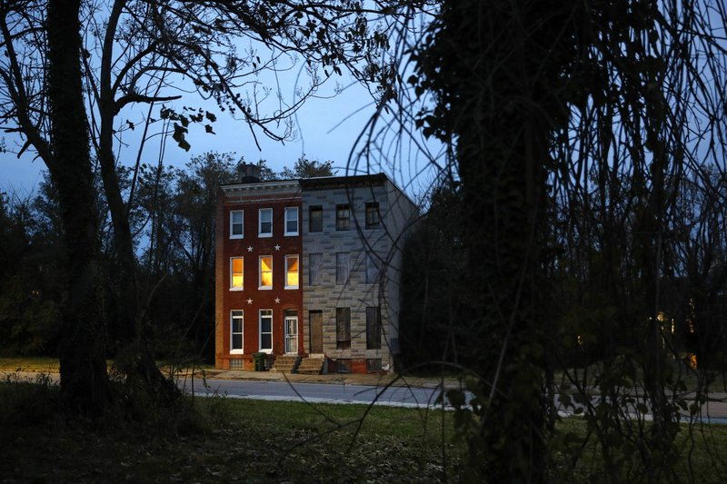In this Nov. 13, 2018 photo, a pair of rowhomes, one occupied, the other boarded up, stand surrounded by vacant lots at dusk in Baltimore. (AP Photo/Patrick Semansky)