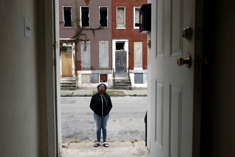 In this Oct. 26, 2018 photo, Nayeka Scott stands outside her front door, across the street from vacant row homes in the Harlem Park neighborhood of Baltimore. (AP Photo/Patrick Semansky)