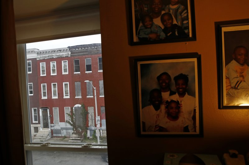 In this Oct. 26, 2018 photo, vacant rowhomes are visible from resident Nayeka Scott's living room in the Harlem Park neighborhood of Baltimore. (AP Photo/Patrick Semansky)