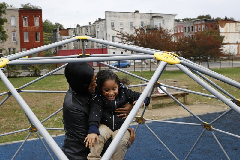 In this Oct. 26, 2018 photo, LaShelle Rollins and her daughter Arrianna, 6, play on a school playground in view of vacant rowhomes in the Harlem Park neighborhood of Baltimore. (AP Photo/Patrick Semansky)
