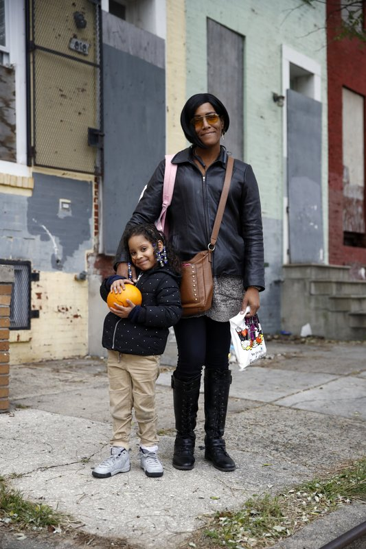 In this Oct. 26, 2018 photo, LaShelle Rollins and her daughter Arrianna, 6, pose for a photo in front of boarded-up rowhomes on their block in the Harlem Park neighborhood of Baltimore. (AP Photo/Patrick Semansky)