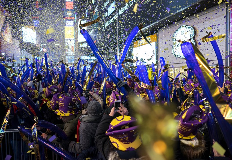 FILE - In this Dec. 31, 2016 file photo, confetti falls during one of the hourly countdowns as revelers take part in a New Year's Eve celebration in New York's Times Square. (AP Photo/Craig Ruttle, File)