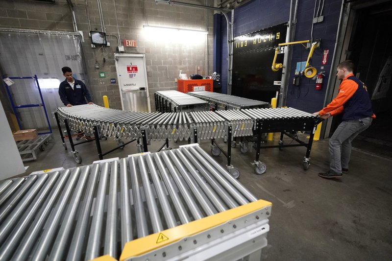 FILE - In this Nov. 9, 2018, file photo, Laurence Marzo, left, and Ty Ford, right, move a conveyor belt into place to help unload a truck carrying merchandise at a Walmart Supercenter in Houston. (AP Photo/David J. Phillip, File)