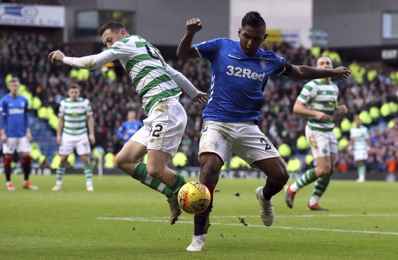 Celtic's Callum McGregor, left, and Rangers' Alfredo Morelos during their Scottish Premiership soccer match at Ibrox Stadium in Glasgow, Scotland, Saturday Dec. (Andrew Milligan/PA via AP)