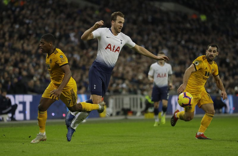 Tottenham Hotspur's Harry Kane, centre falls as he is clipped byWolverhampton Wanderers Ivan Cavaleiro, left, during their English Premier League soccer match between Tottenham Hotspur and Wolverhampton Wanderers at Wembley stadium in London, Saturday, Dec. (AP Photo/Kirsty Wigglesworth)