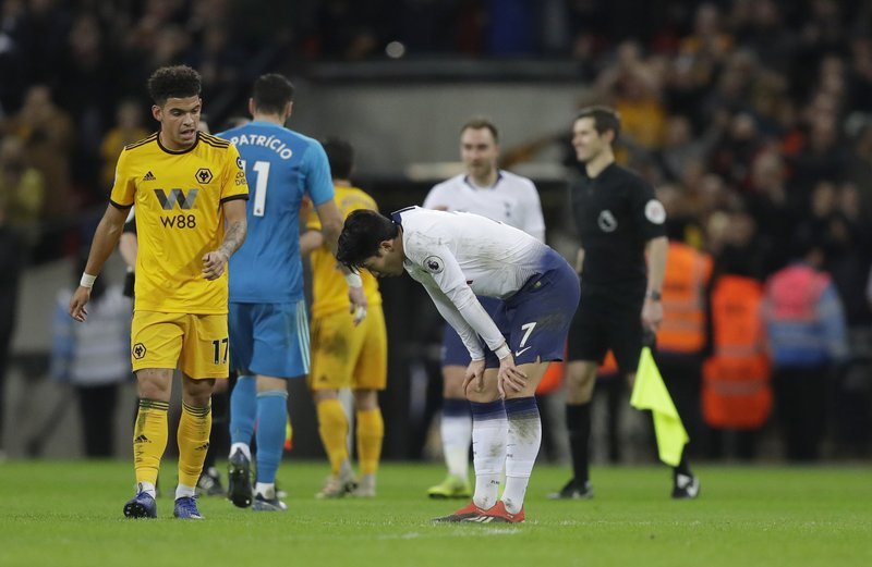 Tottenham Hotspur's Son Heung-min, bends down after the end of the English Premier League soccer match between Tottenham Hotspur and Wolverhampton Wanderers, as Wolverhampton Wanderers Morgan Gibbs-White walks past at Wembley stadium in London, Saturday, Dec. (AP Photo/Kirsty Wigglesworth)