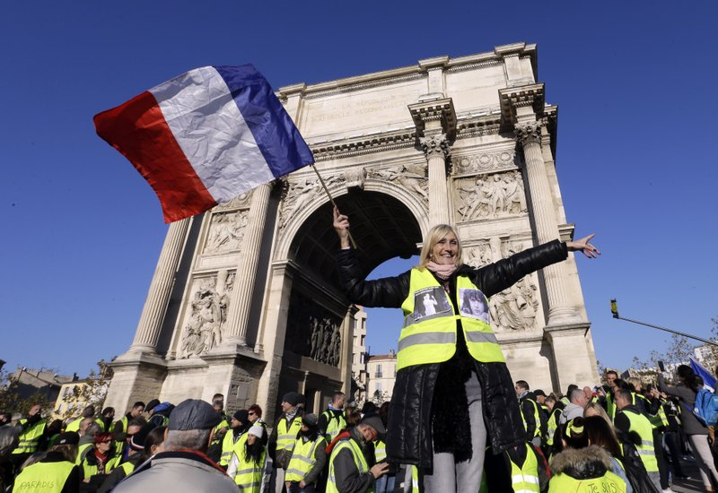 A demonstrator wearing her yellow vest waves a national flag during a protest in front of the Arc de Triomphe of the Porte d'Aix, in Marseille, southern France, Saturday, Dec. (AP Photo/Claude Paris)