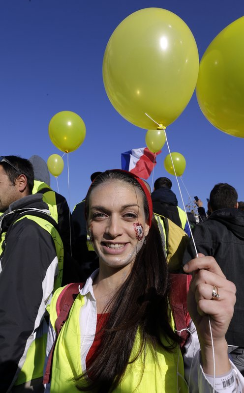 A demonstrator with a yellow balloon and wearing her yellow vest demonstrates during a protest in front of the Arc de Triomphe of the Porte d'Aix, in Marseille, southern France, Saturday, Dec. (AP Photo/Claude Paris)