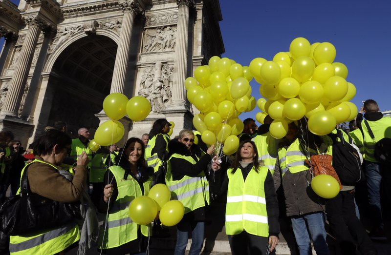 Demonstrators with yellow balloons and wearing their yellow vests demonstrate during a protest in front of the Arc de Triomphe of the Porte d'Aix, in Marseille, southern France, Saturday, Dec. (AP Photo/Claude Paris)