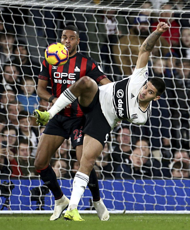 Huddersfield Town's Mathias Zanka Jorgensen, left, and Fulham's Aleksandar Mitrovic in action during their English Premier League soccer match at Craven Cottage in London, Saturday Dec. (Yui Mok/PA via AP)