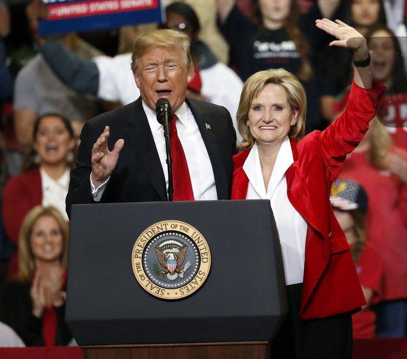 FILE - In this Nov. 26, 2018, file photo, Republican interim senator Cindy Hyde-Smith and President Donald Trump wave during a rally in Biloxi, Miss. (AP Photo/Rogelio V. Solis, File)