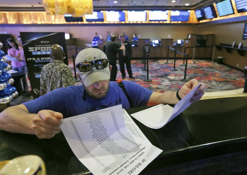 FILE - In this Aug. 3, 2018, file photo, of Marvin Werkley, of Mobile, Ala., looks over wagering sheets at the IP Casino Resort & Spa in Biloxi, Miss. (John Fitzhugh/The Sun Herald via AP, File)