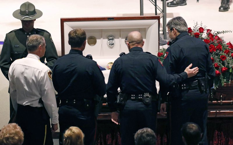 FILE - In this Oct. 4, 2018, file photo, lawmen console one another during visitation prior to the funeral services for Brookhaven Police Corporal Zach Moak at Easthaven Baptist Church in Brookhaven, Miss. (AP Photo/Rogelio V. Solis)