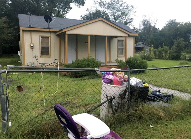 FILE - In this Oct. 16, 2018 photo, toys, a discarded high chair and police evidence tape are part of the trash left outside a home in Shaw, Miss. (Shelby Sansone/WHBQ-Fox 13 via AP, File_