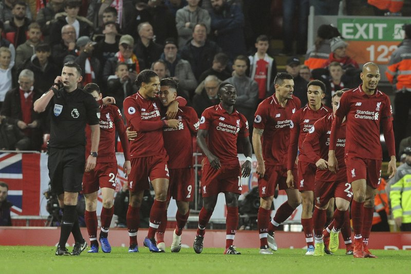 Liverpool's Roberto Firmino, (at centre, No 9) celebrates with teammates after scoring his sides 1st goal during the English Premier League soccer match between Liverpool and Arsenal at Anfield in Liverpool, England, Saturday, Dec. (AP Photo/Rui Vieira)