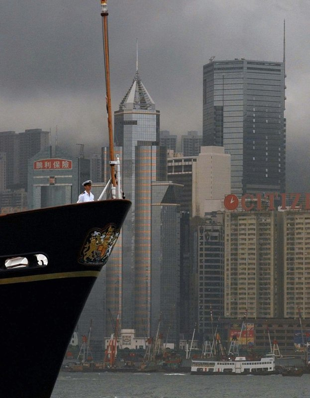 FILE - In this file photo dated Monday, June 23, 1997, an officer stands on the bow above the British Royal crest of Britain's royal yacht Britannia as it sails into Hong Kong past it's city's skyline. (AP Photo/Eric Draper)