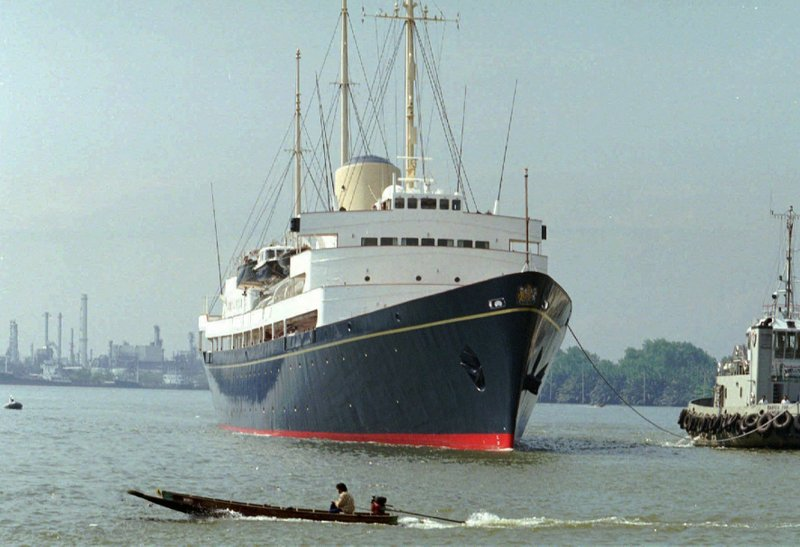 FILE - In this Friday, May 9, 1997 file photo, a long-tailed boat passes by the British Royal Yacht Britannia as it is tugged to port in Bangkok. (AP Photo/Charles Dharapak, file)