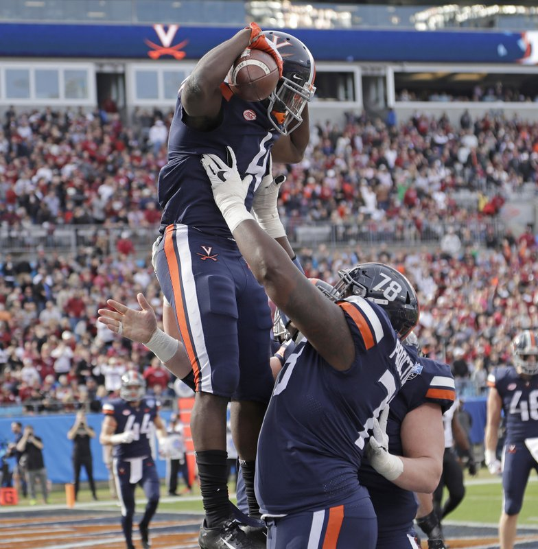 Virginia's Olamide Zaccheaus (4) celebrates his touchdown catch against South Carolina with R.J. Proctor (78) during the first half of the Belk Bowl NCAA college football game in Charlotte, N. (AP Photo/Chuck Burton)