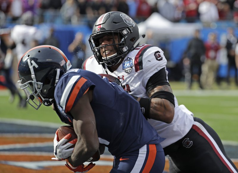 Virginia's Olamide Zaccheaus (4) catches a touchdown pass as South Carolina's R.J. Roderick (10) defends during the first half of the Belk Bowl NCAA college football game in Charlotte, N. (AP Photo/Chuck Burton)