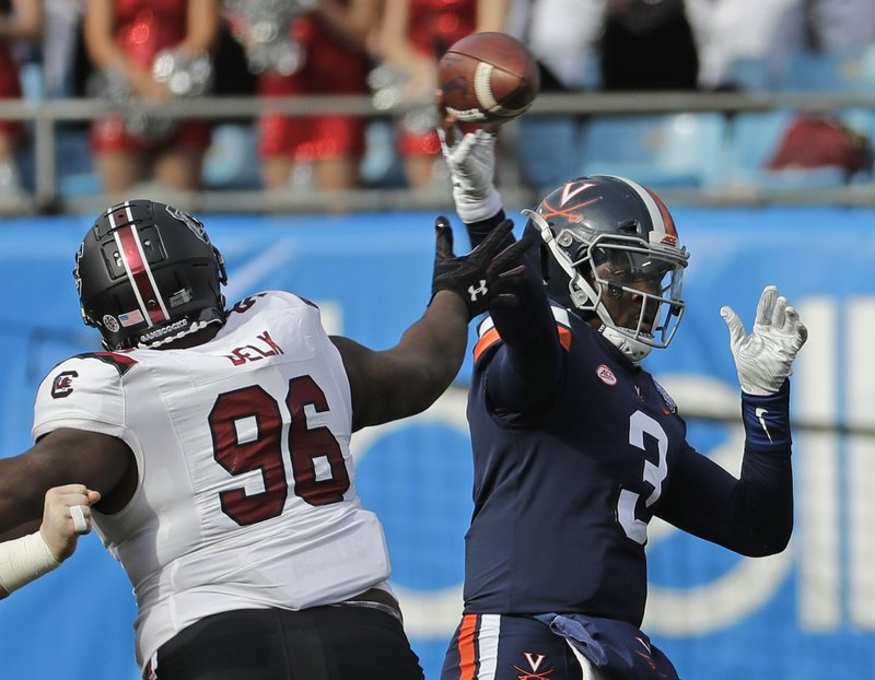 Virginia's Bryce Perkins (3) looks to pass under pressure from South Carolina's Josh Belk (96) during the first half of the Belk Bowl NCAA college football game in Charlotte, N. (AP Photo/Chuck Burton)