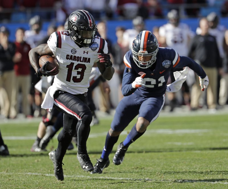 South Carolina's Shi Smith (13) runs as Virginia's Juan Thornhill (21) chases during the first half of the Belk Bowl NCAA college football game in Charlotte, N. (AP Photo/Chuck Burton)