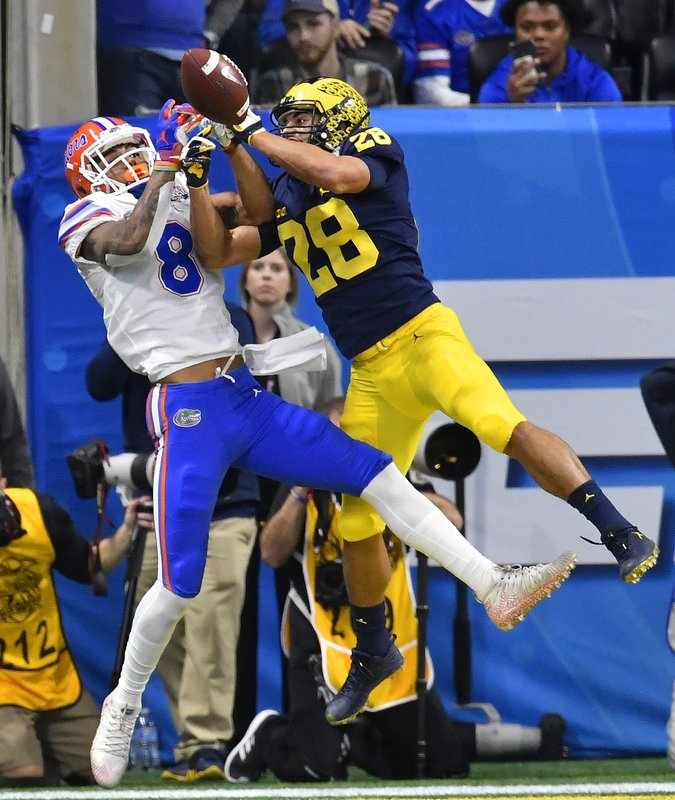 Michigan defensive back Brandon Watson (28) breaks up a pass in the end zone intended for Florida wide receiver Trevon Grimes (8) during the first half of the Peach Bowl NCAA college football game, Saturday, Dec. (AP Photo/Mike Stewart)