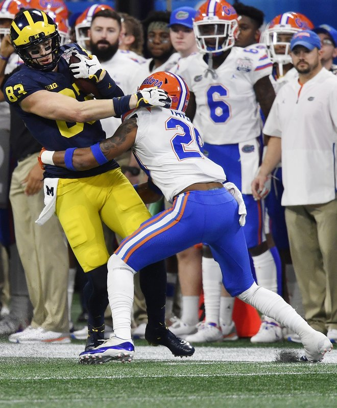 Florida defensive back Jeawon Taylor (29) tackles Michigan tight end Zach Gentry (83) during the first half of the Peach Bowl NCAA college football game, Saturday, Dec. (AP Photo/Mike Stewart)