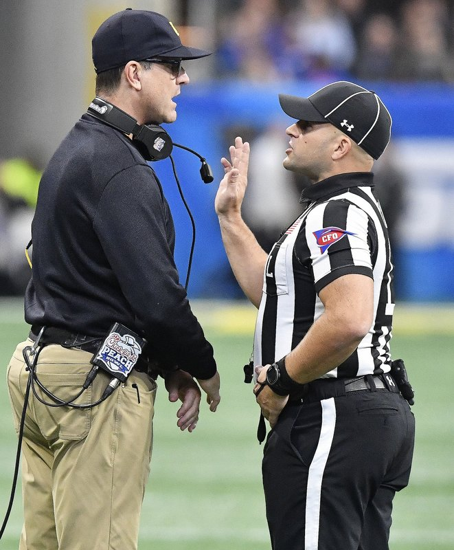 Michigan head coach Jim Harbaugh speaks with an official during the first half of the Peach Bowl NCAA college football game against Florida, Saturday, Dec. (AP Photo/Mike Stewart)