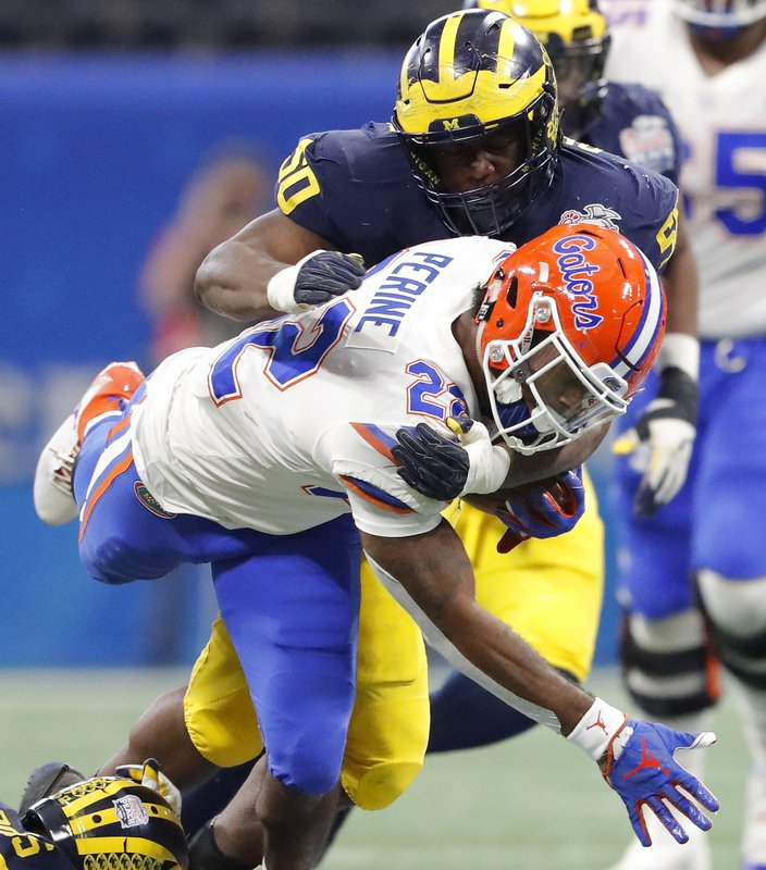 Michigan defensive lineman Michael Dwumfour (50) tackles Florida running back Lamical Perine (22) during the first half of the Peach Bowl NCAA college football game, Saturday, Dec. (AP Photo/John Bazemore)