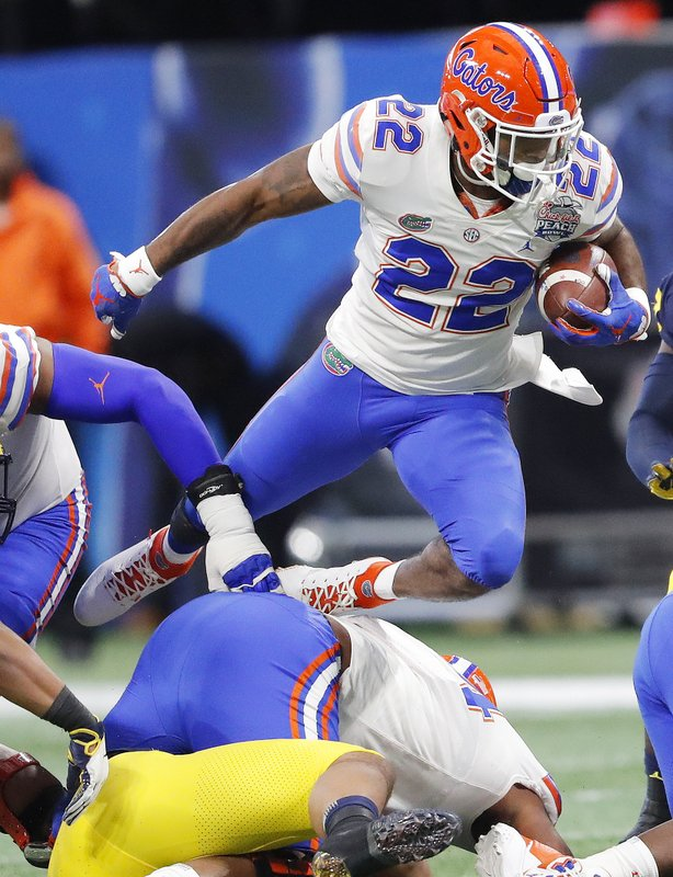 Florida running back Lamical Perine (22) leaps over the line during the first half of the Peach Bowl NCAA college football game against Michigan, Saturday, Dec. (AP Photo/John Bazemore)