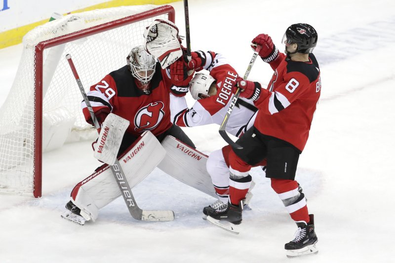 Carolina Hurricanes left wing Warren Foegele, center, tries to avoid a collision with New Jersey Devils goaltender MacKenzie Blackwood, left, during the third period of an NHL hockey game, Saturday, Dec. (8) tries to avoid the collision, too. The Devils won 2-0. (AP Photo/Julio Cortez)