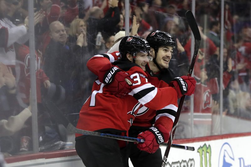 New Jersey Devils center Pavel Zacha, left, of the Czech Republic, celebrates his second period goal with Brian Boyle during an NHL hockey game against the Carolina Hurricanes, Saturday, Dec. (AP Photo/Julio Cortez)