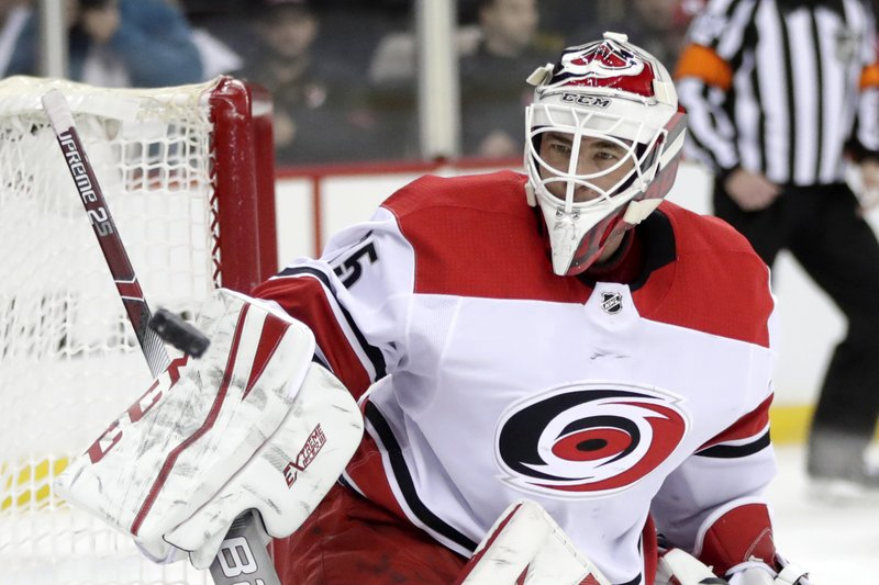Carolina Hurricanes goaltender Curtis McElhinney blocks a shot from the New Jersey Devils during the second period of an NHL hockey game, Saturday, Dec. (AP Photo/Julio Cortez)