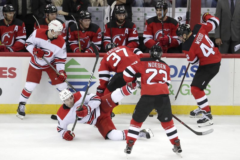Carolina Hurricanes left wing Jordan Martinook, bottom, loses his balance while competing for the puck with New Jersey Devils center Pavel Zacha (37), of the Czech Republic, during the third period of an NHL hockey game, Saturday, Dec. (AP Photo/Julio Cortez)