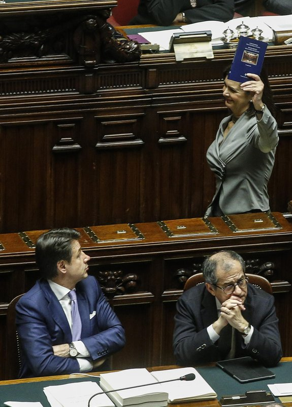 Former lower chamber President Laura Boldrini, top right, shows the Constitution to Italian Premier Giuseppe Conte, left, and Economy Minister Giovanni Tria to protest  during the vote of confidence on the budget law at the Italian lower chamber in Rome, Saturday, Dec. (Fabio Frustaci/ANSA via AP)