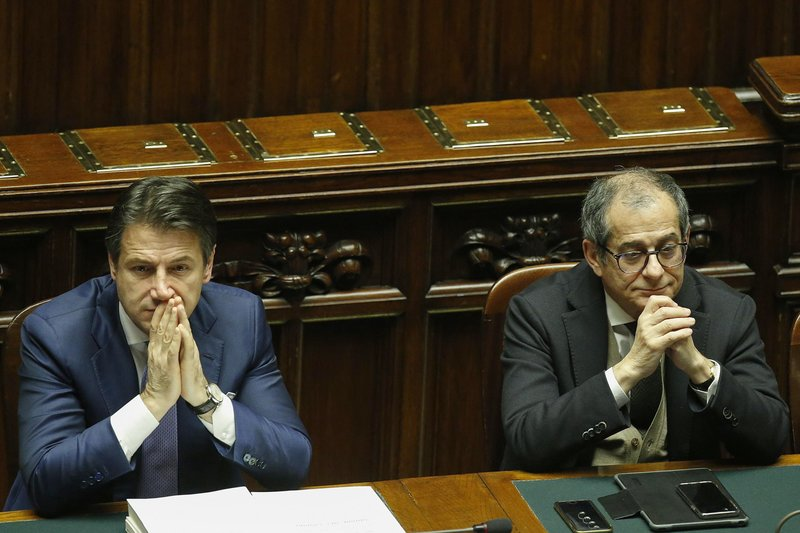 Italian Premier Giuseppe Conte, left, and Economy Minister Giovanni Tria sit during the vote of confidence on the budget law at the Italian lower chamber in Rome, Saturday, Dec. (Fabio Frustaci/ANSA via AP)