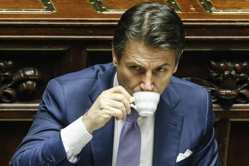 Italian prime minister Giuseppe Conte sips coffee during the vote of confidence on the budget law at the Italian lower chamber in Rome, Saturday, Dec. (Fabio Frustaci/ANSA via AP)