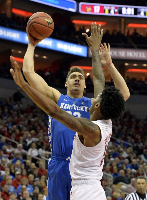Kentucky forward Reid Travis (22) shoots over the defense of Louisville center Malik Williams (5) during the first half of an NCAA college basketball game in Louisville, Ky. (AP Photo/Timothy D. Easley)