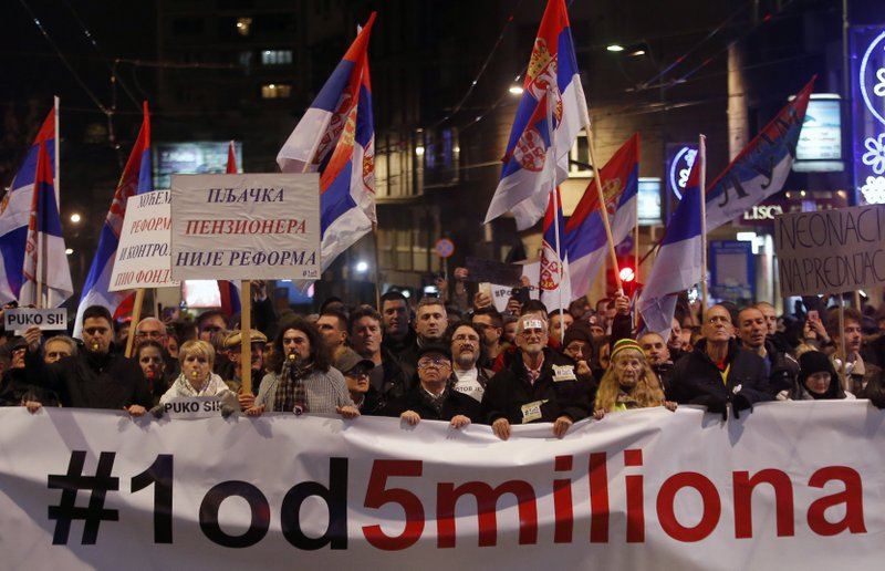 People hold a banner that reads: ''#1out of 5 million'' during a protest against populist President Aleksandar Vucic in Belgrade, Serbia, Saturday, Dec. (AP Photo/Darko Vojinovic)