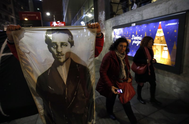 A man from opponents group shows picture of Gavrilo Princip, the Bosnian-Serb nationalist who assassinated Archduke Franz Ferdinand in 1914, during a protest march against populist President Aleksandar Vucic in Belgrade, Serbia, Saturday, Dec. (AP Photo/Darko Vojinovic)