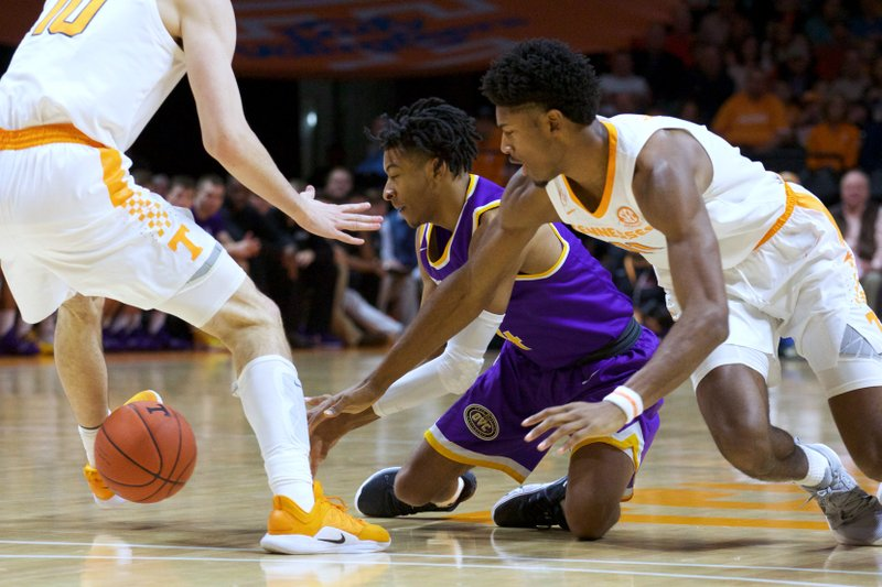 Tennessee Tech guard J.R. Clay (4) and Tennessee forward Kyle Alexander (11) scramble for the ball in the first half of an NCAA college basketball game Saturday, Dec. (AP Photo/Shawn Millsaps)