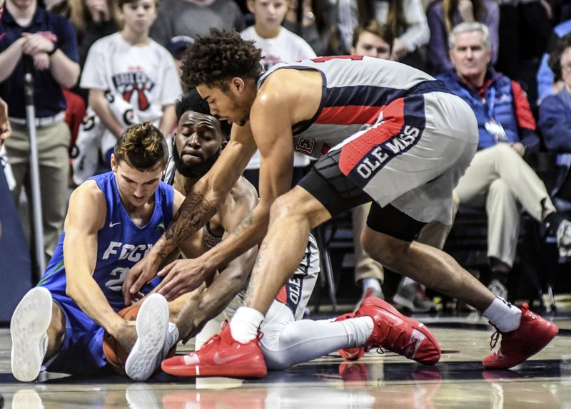 Florida Gulf Coast's Caleb Catto (2) and Mississippi's D.C. Davis (20) and KJ Buffen (14) get tied up going for the ball  during an NCAA college basketball game  Saturday, Dec. (Bruce Newman/Oxford Eagle via AP)