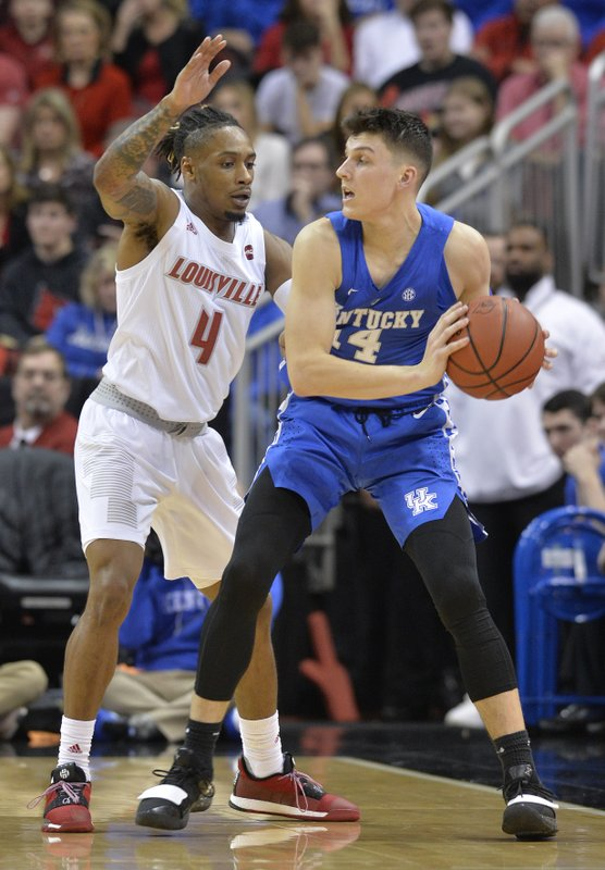 Kentucky guard Tyler Herro (14) looks for help from the defense of Louisville guard Khwan Fore (4) during the second half of an NCAA college basketball game in Louisville, Ky. (AP Photo/Timothy D. Easley)
